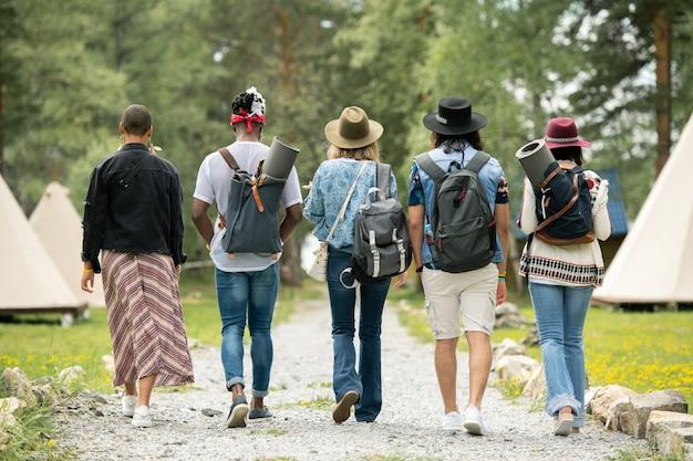 Achteraanzicht van jonge mensen met boekentassen die over festivalcamping lopen terwijl ze een tent zoeken