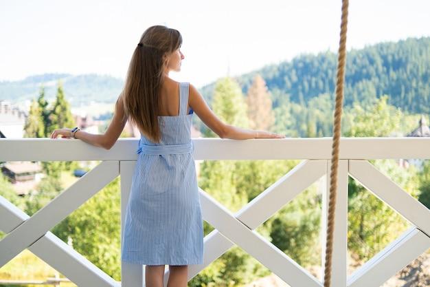 Achteraanzicht van jonge mooie vrouw op balkon genieten van uitzicht op de natuur. concept van het rusten op frisse lucht.