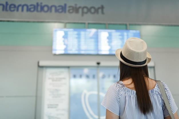 Achteraanzicht van jonge reizigerstoeristenvrouw met hoed die op schema kijkt, tijdschema wachtend in de lobbyhal op de internationale luchthaven