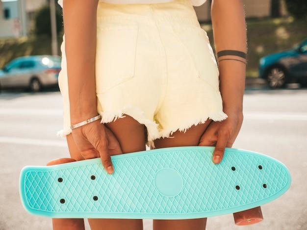 Achteraanzicht van jonge sexy vrouw kont in korte broek. meisje met blauwe cent skateboard poseren in de straat