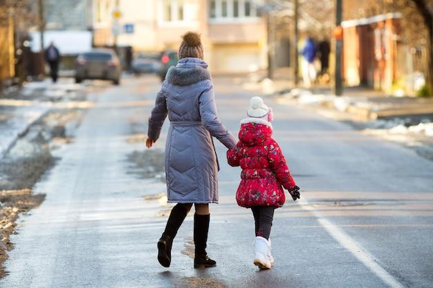 Achteraanzicht van jonge slanke aantrekkelijke vrouw moeder en klein kind meisje dochter in warme kleding lopen samen hand in hand glibberige straat oversteken op zonnige winterdag op onscherpe stedelijke achtergrond.