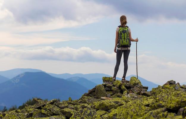 Achteraanzicht van jonge slanke backpacker toeristische meisje met stok staande op rotsachtige top