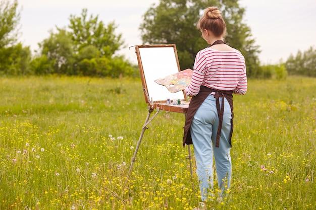 Achteraanzicht van jonge slanke vrouw kunstenaar foto tekenen op canvas in de natuur, meisje met penseel in de hand en palet van verven werken