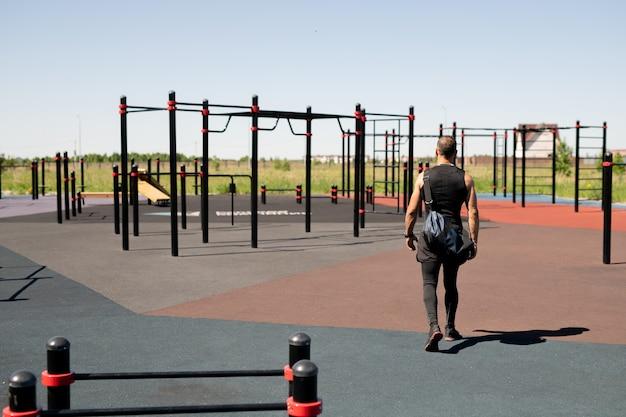 Achteraanzicht van jonge sportman in activewear komt naar sportfaciliteiten op sportveld buitenshuis