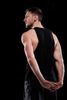 Achteraanzicht van jonge sportman in zwarte activewear die afzonderlijk met zijn handen achter het onderste deel van de rug traint