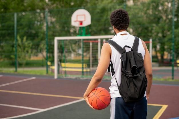Achteraanzicht van jonge sportman met zwarte rugzak en bal die naar basketbalveld komt om te spelen