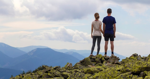 Achteraanzicht van jonge toeristische paar, atletische man en slank meisje staan hand op rotsachtige bergtop genieten van adembenemend zomer bergpanorama. toerisme, reizen en gezonde levensstijl concept.