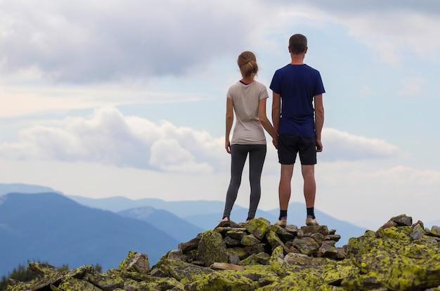 Achteraanzicht van jonge toeristische paar hand in hand op rotsachtige bergtop