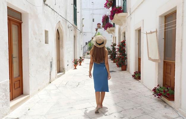 Achteraanzicht van jonge toeristische vrouw op oude straat in de oude stad