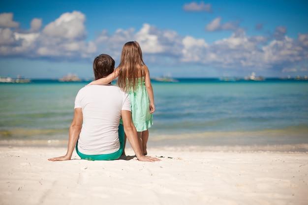 Achteraanzicht van jonge vader en zijn dochtertje kijken naar de zee