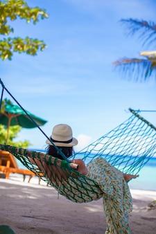Achteraanzicht van jonge vrouw genieten van vakantie in de hangmat