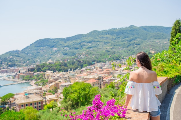 Achteraanzicht van jonge vrouw in een prachtige stad. toerist die toneelmening van rapallo, cinque terre, ligurië, italië bekijken