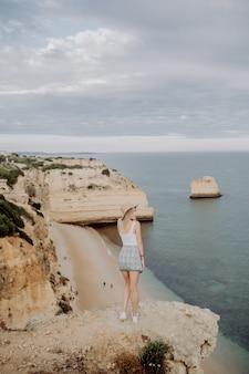 Achteraanzicht van jonge vrouw in hoed en schattige zomerjurk staande op de steen