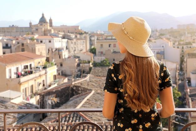 Achteraanzicht van jonge vrouw in jurk en hoed kijkend vanaf terras stadsgezicht van palermo, italië