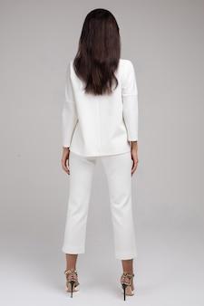 Achteraanzicht van jonge vrouw in wit pak staande tegen de grijze achtergrond in de studio. mode- en stijlconcept