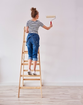 Achteraanzicht van jonge vrouw met verfroller schilderij muur Premium Foto