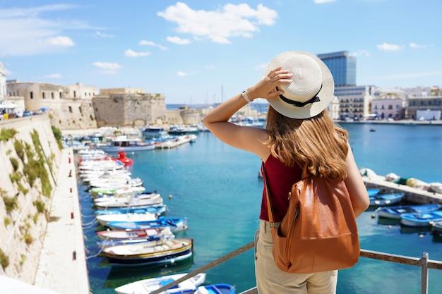 Achteraanzicht van jonge vrouwelijke backpacker in gallipoli, salento, italië