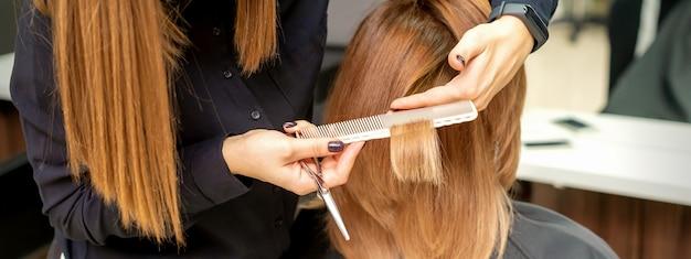 Achteraanzicht van kapper knipt rood of bruin haar aan jonge vrouw in de schoonheidssalon. kapsel in kapsalon. zachte focus