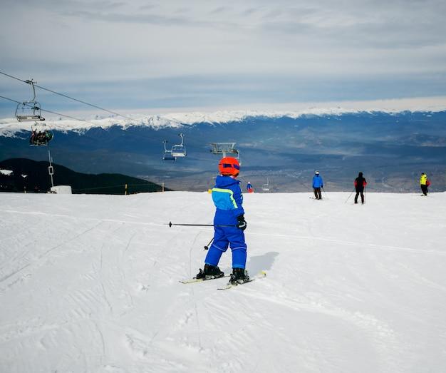 Achteraanzicht van klein kind skiën in de bergen met veiligheidsuitrusting.