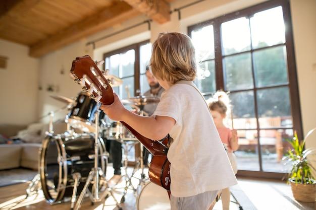 Achteraanzicht van kleine jongen met een gezin binnenshuis, gitaar spelend.