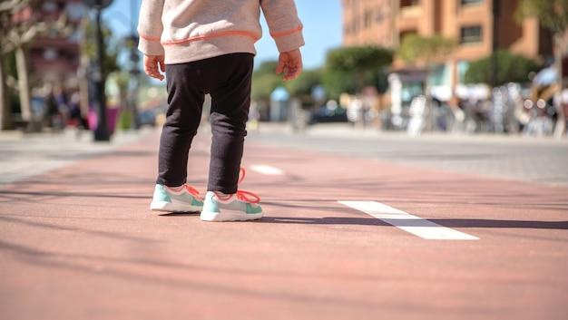 Achteraanzicht van kleine meisjesbenen met sneakers en zwarte leggins die op een zonnige dag over een stadsbaan staan