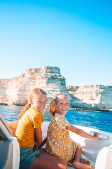 Achteraanzicht van kleine schattige meisjes genieten van zeilen op boot in de open zee