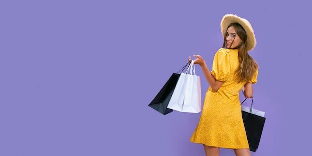 Achteraanzicht van lachend volwassen meisje houdt pakketten vast na het winkelen korting black friday sale concept