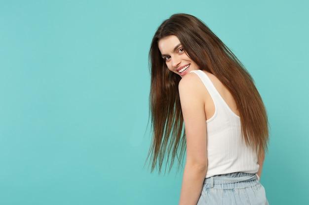 Achteraanzicht van lachende grappige jonge vrouw in lichte casual kleding terugkijkend geïsoleerd op blauwe turquoise muur achtergrond in studio. mensen oprechte emoties, lifestyle concept. bespotten kopie ruimte.
