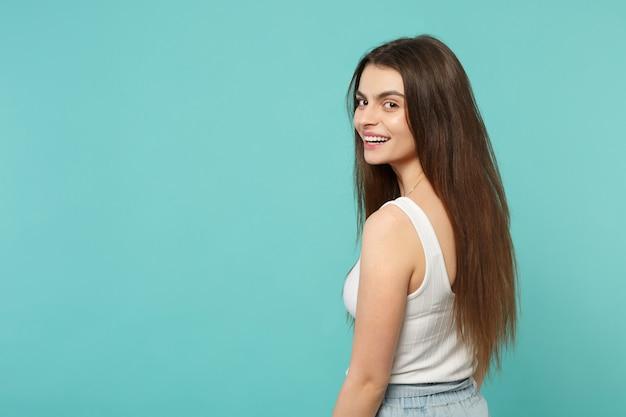 Achteraanzicht van lachende mooie jonge vrouw in lichte casual kleding terugkijkend geïsoleerd op blauwe turquoise muur achtergrond in studio. mensen oprechte emoties, lifestyle concept. bespotten kopie ruimte.