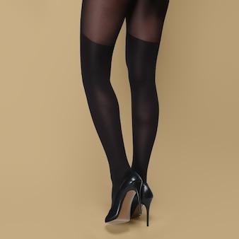 Achteraanzicht van lange slanke vrouwelijke benen in panty's en schoenen met hoge hakken.