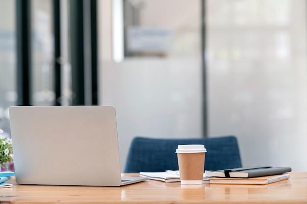 Achteraanzicht van laptop computer notebook op houten tafel in moderne kantoorruimte.
