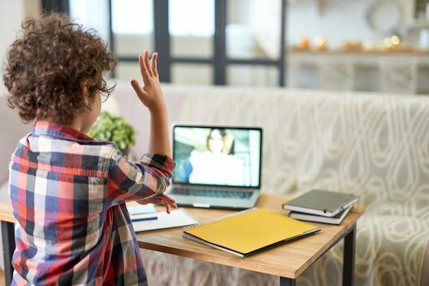 Achteraanzicht van latijnse schooljongen die zijn hand opsteekt tijdens online les via videochat-app. kind dat laptop gebruikt terwijl hij thuis studeert. online onderwijs, technologie, thuisonderwijs. selectieve focus
