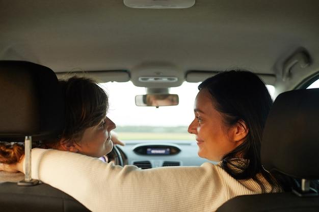 Achteraanzicht van lesbisch koppel reizen met de auto en genieten van hun rit samen
