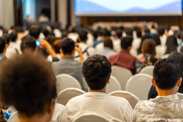 Achteraanzicht van luisterend publiek sprekers op het podium met presentatie via projector