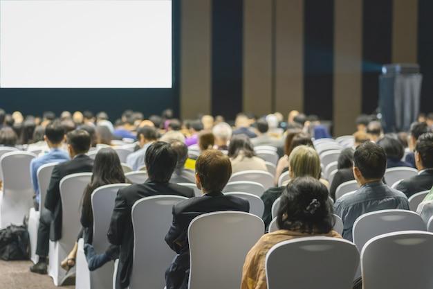 Achteraanzicht van luistergesprekken luidsprekers op het podium in de conferentiezaal of seminarvergadering