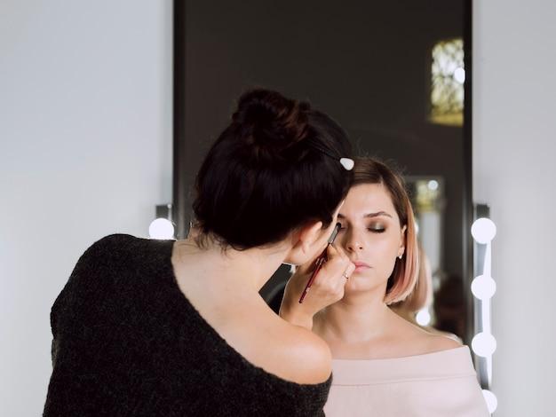 Achteraanzicht van make-up artist aan het werk