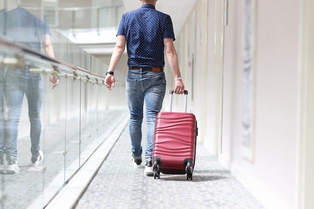 Achteraanzicht van man die koffer door hotelgang trekt