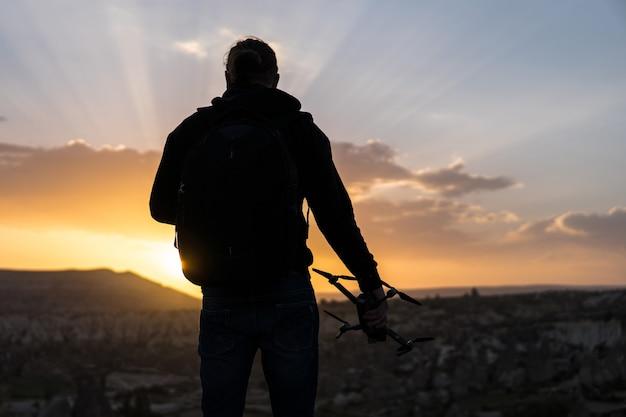 Achteraanzicht van man die tegen zonsopgang staat met drone in de hand