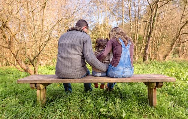 Achteraanzicht van man en vrouw knuffelen met een klein meisje zittend op het midden van een houten bankje in het park. familie vrije tijd buitenshuis concept.
