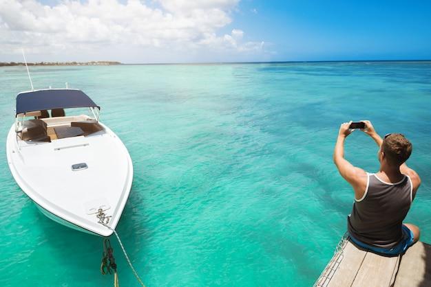 Achteraanzicht van man fotograferen van fantastisch uitzicht op de oceaan
