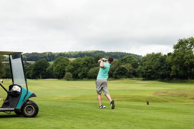Achteraanzicht van man golfen