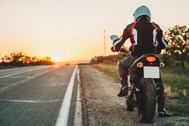 Achteraanzicht van man in beschermende jas, laarzen en helm rijden langs de weg bij zonsondergang op lege snelweg verlichte achtergrond
