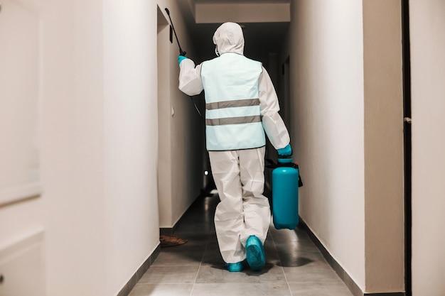 Achteraanzicht van man in steriele beschermende witte uniforme desinfecterende hal van het gebouw om covid 19 te beschermen tegen verspreiding.