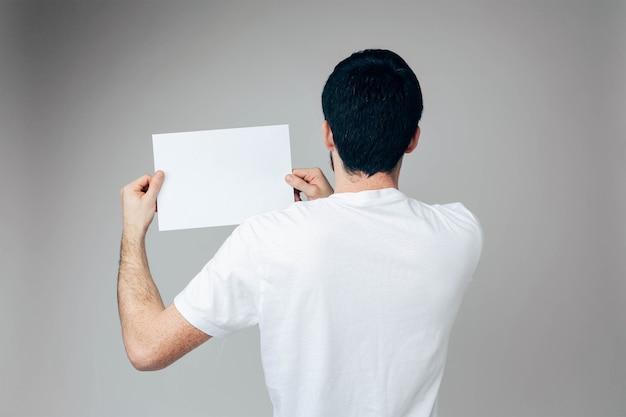 Achteraanzicht van man in wit overhemd houdt lege pagina in handen aan de linkerkant