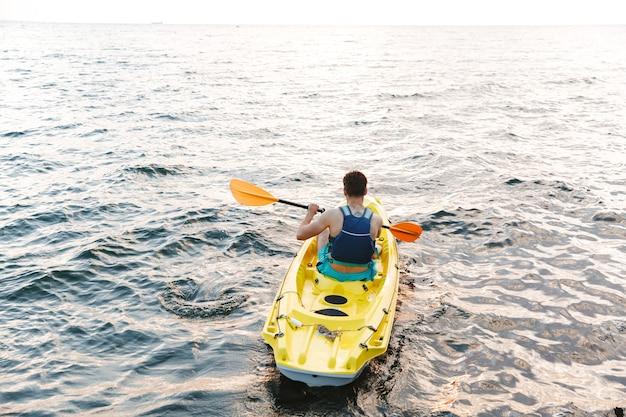 Achteraanzicht van man kayaker peddelen