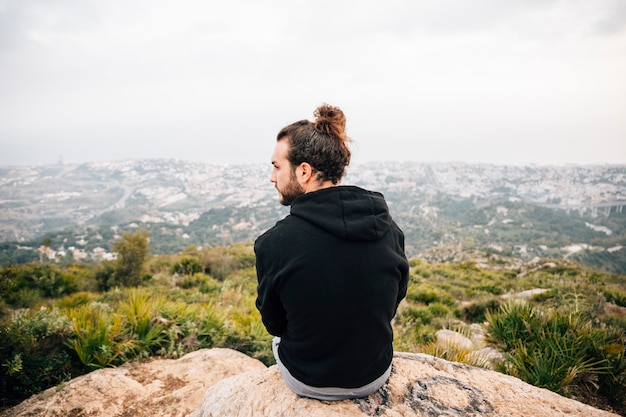 Achteraanzicht van man zit op de top van rots met uitzicht op de bergen