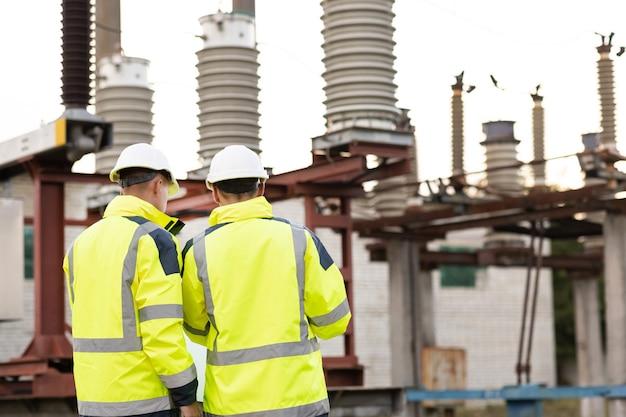 Achteraanzicht van mannelijke civiel ingenieur en jonge bouwarchitect gebruiken papieren plan op een stadsconstructie