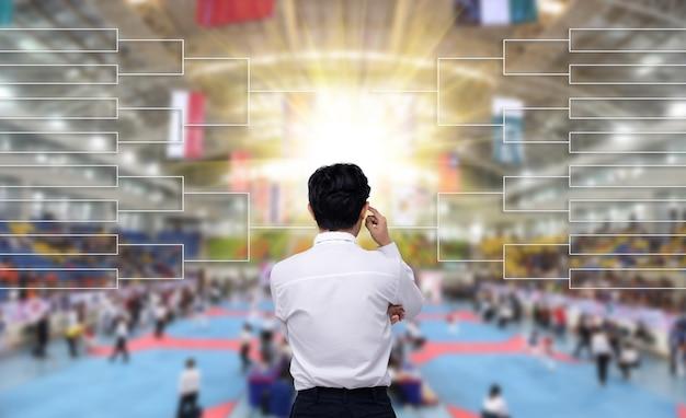 Achteraanzicht van mannelijke coach in wit overhemd kijken naar schedule tree chart of timetable, zodat hij de strategie van taekwondo, karate, judo gevechten op kwartfinale wedstrijd in internationaal stadion kan plannen