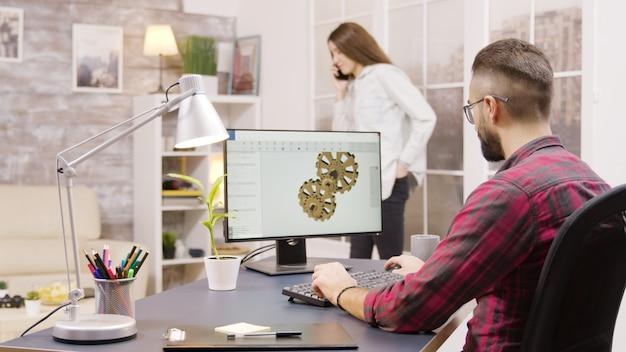 Achteraanzicht van mannelijke ingenieur die vanuit huis aan een mechanisch concept werkt. vriendin op de achtergrond.