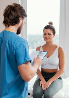 Achteraanzicht van mannelijke osteopaat therapeut met vrouwelijke patiënt klembord ondertekenen in de kliniek